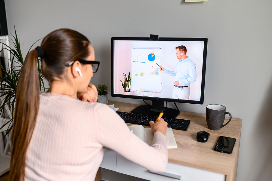 picture of a female sitting infront of a computer watching an online course
