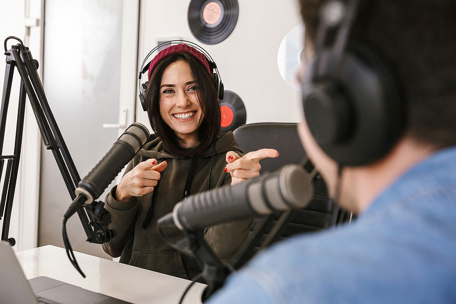 picture of a male and female sitting at a desk talking into two large microphones for their podcast