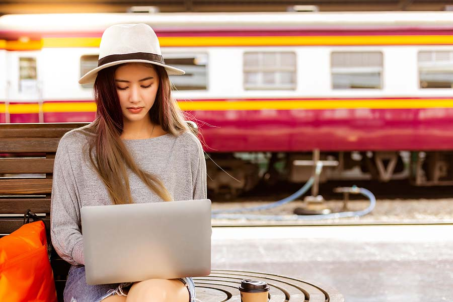 picture of a woman sitting at a train station working on her laptop doing some proofreading work