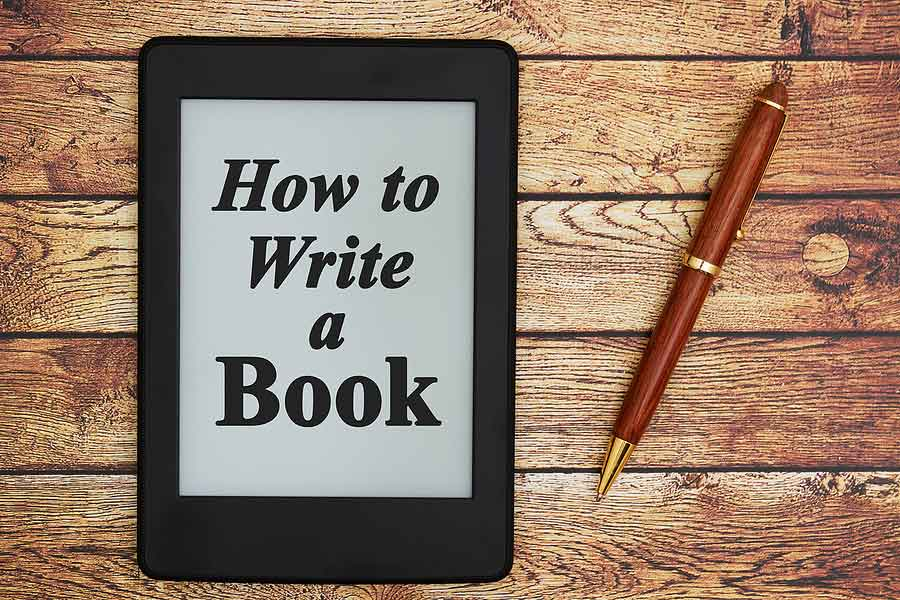picture of a pen and a picture kindle reader with the words how to write a book displayed on the screen