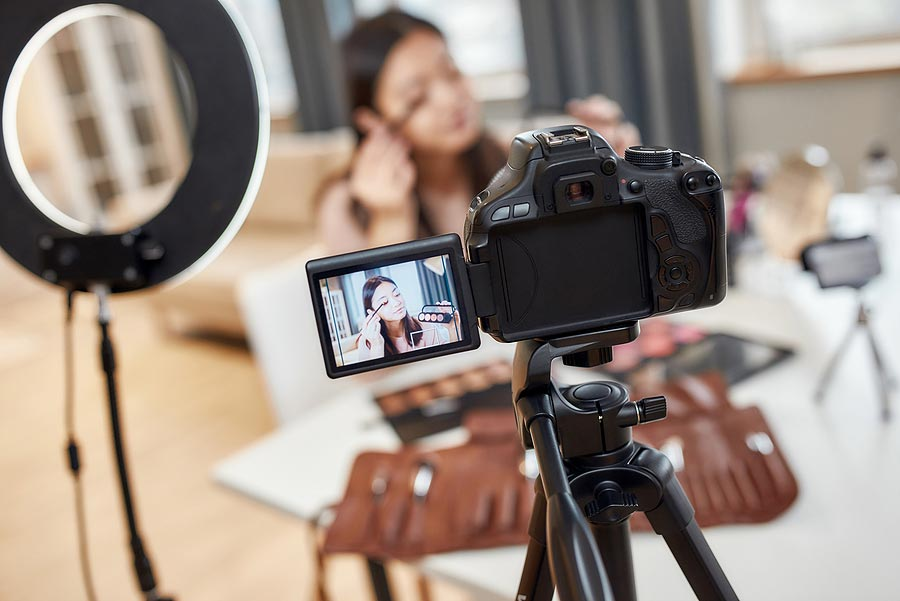 picture of a camera and a light with a girl teaching makeup online for her youtube channel