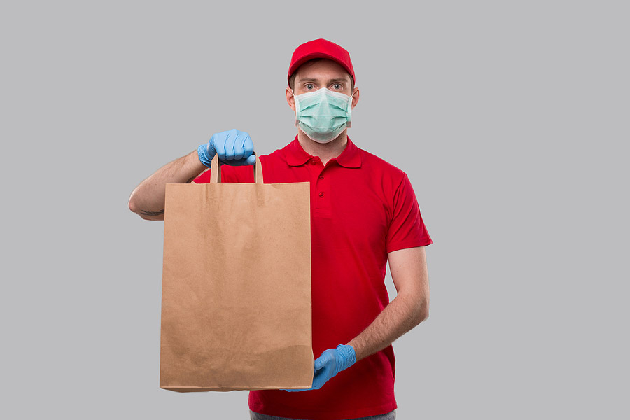 picture of a delivery person holding a brown paper bag with food inside of it