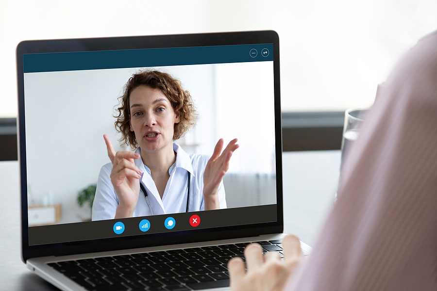 a picture of a laptop receiving a skype call from a doctor who is giving an online consultation to a person