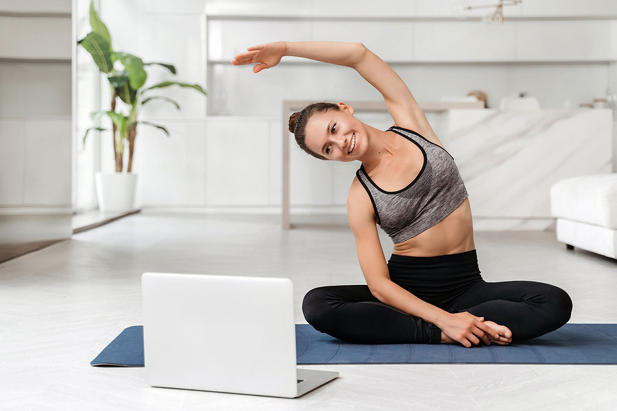 picture of a woman doing a yoga pose in front of her laptop so her student can see the pose