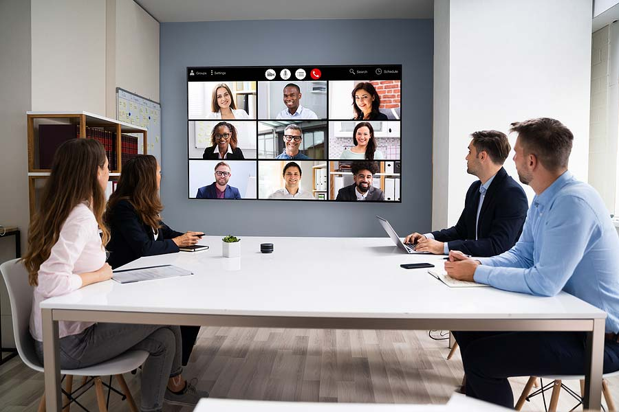 picture of a conferencing equipment in a room with people watching the conference screen
