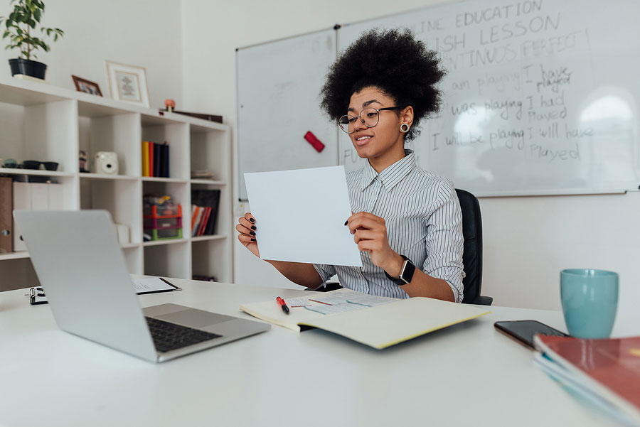woman sitting in front of a laptop at her desk holding up a piece of paper with an English word on it while she shows her student the word for them to guess